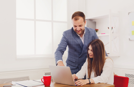 Businessman supervising his female assistant's work on laptop computer